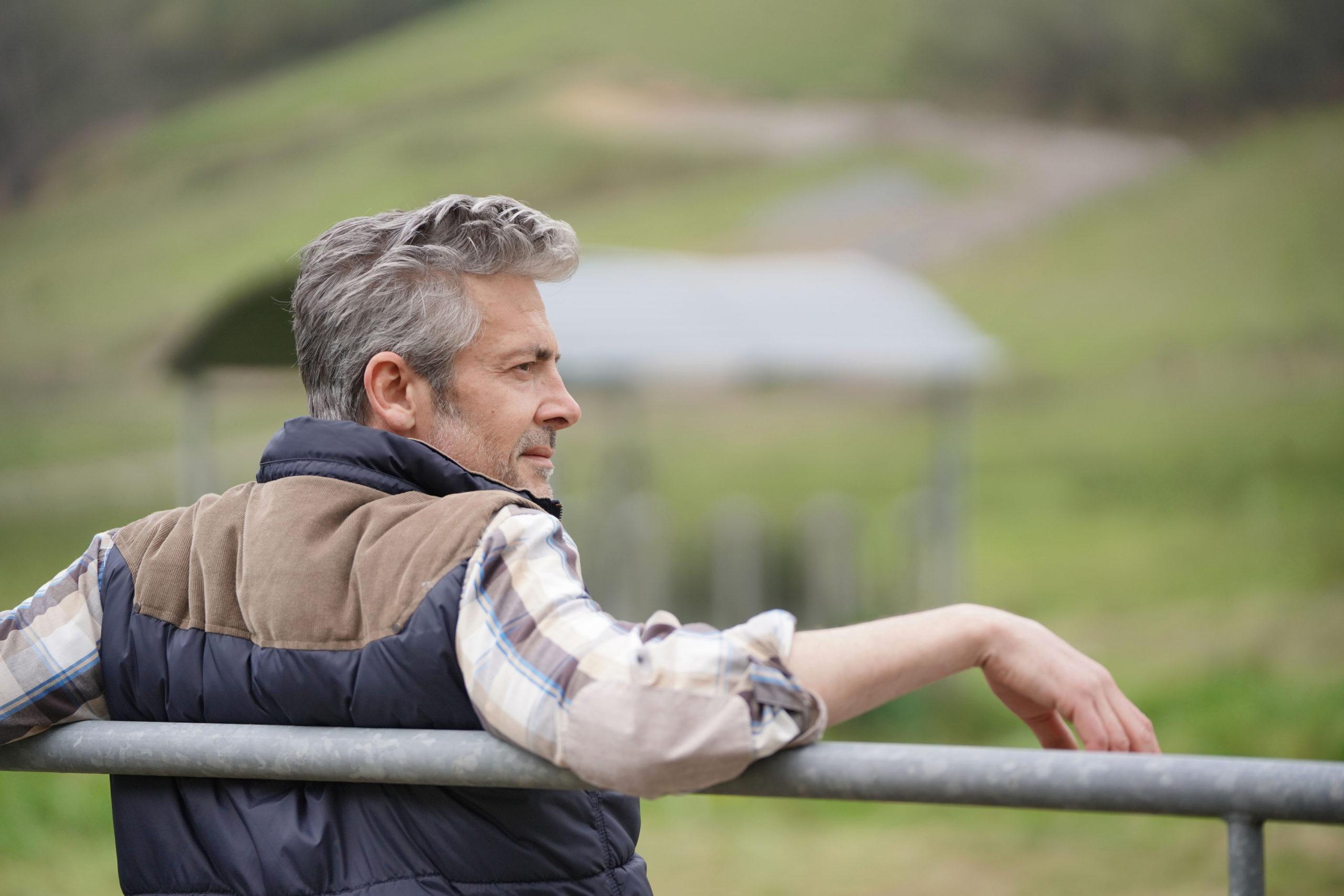 acreage owner leaning on fence